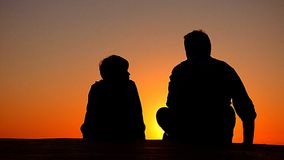 Silhouette of Man and Boy Sitting at Sunset Stock Images