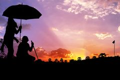 Silhouette Man with caddies playing golf. On a golf course beautiful twilight and sunset Royalty Free Stock Photography