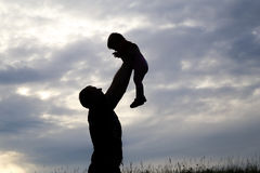 Silhouette of a man carrying a child. Silhouette of a men carrying a child on the nature of the evening. Raises in her arms to the sky Stock Image