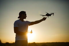 Silhouette of a man catching drone with one hand and remote controller in another hand on sunset. Safe quadcopter Stock Photos