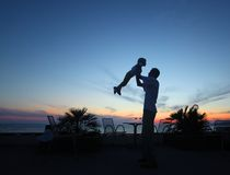Silhouette of man with child in hands on sunset Stock Photo
