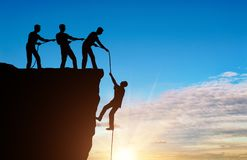 Silhouette of a man climbers pulling out of a cliff of another climber royalty free stock photo