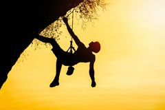 Silhouette of man climbing at sunset. The rock climber during ro. Ck conquest. Climbing sport concept Stock Image