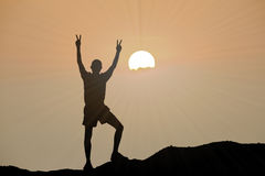 Silhouette of man is climbing to peak of hill. With sunset or sunrise background Royalty Free Stock Images