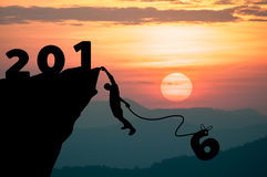 Silhouette Man climbs into cliff to make the word New Year 2016. Stock Photo