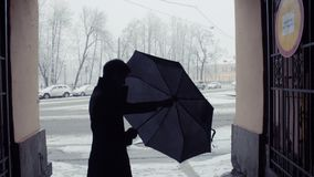 Silhouette of man closing umbrella under snowfall. Snow covered park background. Silhouette of man with cup of coffee standing closing umbrella after snowfall stock video
