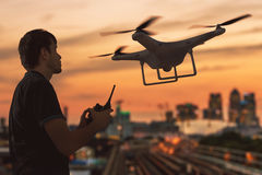 Silhouette of a man controlling flying drone. 3D rendered illustion of drone. Royalty Free Stock Photo