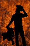 Silhouette man cowboy saddle touch hat. A silhouette of a cowboy with a fire background holding on to his hat and saddle Stock Images