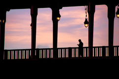 Silhouette of man crossing the bridge. At sunset Stock Images