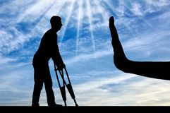 Concept of discrimination and disrespect for people with disabilities. A silhouette of a man with crutches and a hand gesture of stop. The concept of Stock Images