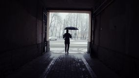 Silhouette of man with coffee cup opening umbrella. Snowfall and on background. Silhouette of man with a cup of coffee standing and opening umbrella before stock footage