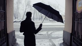 Silhouette of man opening umbrella under snowfall. Snow covered park background. Silhouette of man with a cup of coffee standing and opening umbrella before stock video footage