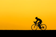 A Silhouette of man cycling. On the lawn in sunset Stock Images