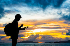 Silhouette man with digital tablet. In hands at sunset beach Royalty Free Stock Image