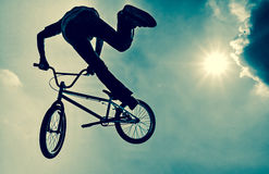 Silhouette of a man doing an BMX extreme jump. stock image