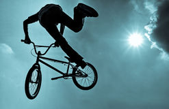 Silhouette of a man doing an BMX extreme jump. Royalty Free Stock Images