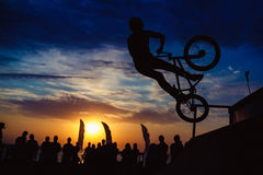 Silhouette of man doing extreme jump with bike. Silhouette of man doing extreme jump with mountain bike at ramp Stock Photography