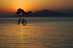 Silhouette of a man doing a jump with a bike Stock Photos