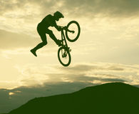 Silhouette of a man doing a jump with a bmx bike. Against sunset sky Royalty Free Stock Photo