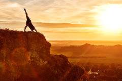 Silhouette of man doing yoga meditation against beautiful sky with clouds. Royalty Free Stock Photography