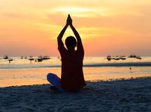 Silhouette of man doing yoga at sunset beach Royalty Free Stock Photography