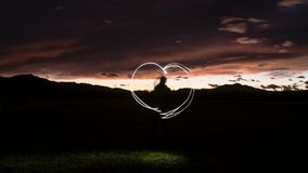 Silhouette of a man draws a heart shape with a flashlight throug Stock Photo