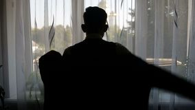 Silhouette of a man dressed in the room.  stock footage