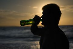 Silhouette of a man drinking beer Stock Photo