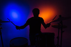 Silhouette of man drummer sitting and playing drums with sticks Stock Photo