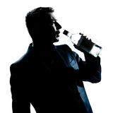 Silhouette man drunk pouring empty alcohol botlle Stock Photo