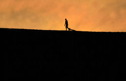 Silhouette of Man on Dune. Silhouette of man dragging a sand board on top of a sand dune Royalty Free Stock Photo