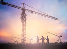 Silhouette man engineer looking construction worker under tower Royalty Free Stock Photo