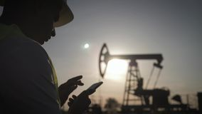 Silhouette of man engineer with phone overseeing the site of crude oil production at sunset. stock video