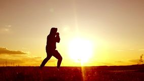 Silhouette of man exercising thai boxing. Silhouette of martial arts man training boxing on the beach over beautiful sunset backgr. Ound. Training karate or stock video footage