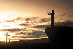 Silhouette of man facing the cross and praying stock image