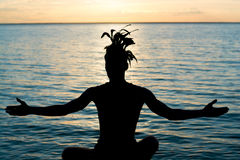 Silhouette of a man with feathers on his head, who sits in front. Of the sea at sunset, his arms outstretched. Young man in clothes of an american indian style Stock Image