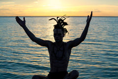 Silhouette of a man with feathers on his head, who sits in front. Of the sea at sunset, his hands raised up. Young man in clothes of an american indian style Royalty Free Stock Photo