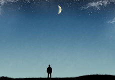 Silhouette of a man on the field with grass, starry sky and moon.  Royalty Free Stock Photo