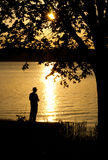 Silhouette of a man fishing. Against setting sun Stock Images