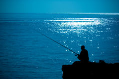 Silhouette man fishing Stock Images