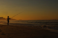 Silhouette man fishing on the beach. Fisherman silhouette on the beach Stock Images