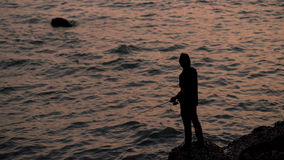 Silhouette Man fishing at dusk Royalty Free Stock Photos