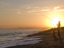 Silhouette of man fishing with fishing rod at ocean at sunset Royalty Free Stock Photography