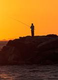 Silhouette of Man fishing stock images