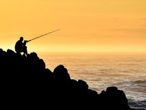 Silhouette of man fishing whilst sitting on coastal rocks. Silhouette of man fishing whilst sitting on coastal rocks in the early hours of morning Stock Photos