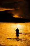 Silhouette of Man Flyfishing in River. Silhouette of Man Flyfishing Fishing in River Royalty Free Stock Image