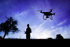 Silhouette of man with flying drone in nature at dusk. Silhouette of young man with flying drone in nature at dusk against blue sky Stock Photo