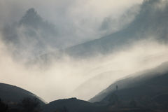 Silhouette of a man in a fog against the backdrop of mountain sl Stock Photography