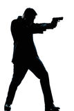 Silhouette man full length shooting with gun. One caucasian spy criminal policeman detective man aiming shooting gun  full length silhouette in studio isolated