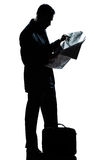 Silhouette man full length standing reading newspaper Stock Image